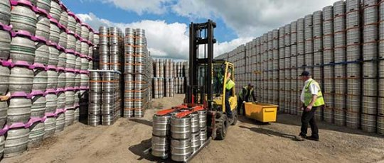 Men loading a fork lift with barrels